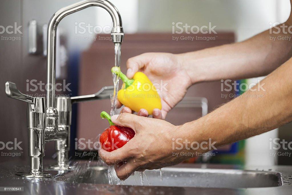 Kitchen porter washing pepper under running tap stock photo