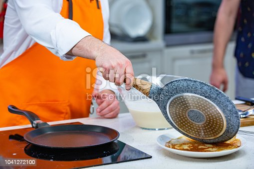 kitchen Preparation: the chef in a bright apron fries fresh pancakes in two pans