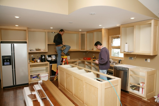 Cabinet maker installing custom made kitchen island and cabinets, while electrician installs in-cabinet lighting.   Very shallow DOF quickly drops off to nice soft focus.