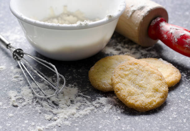 Kitchen Scene with Flour and Sugar Cookies Crisp sugar cookies are surrounded by flour and cooking utensils on this dark gray countertop. The cookies have a fantastic texture that lets the viewer know they are crunchy. sugar cookie stock pictures, royalty-free photos & images