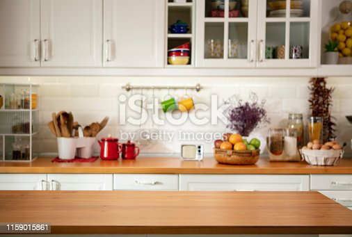 Kitchen featuring utensils and decorative items on the counter, suitable for inserting items or people, focus on front counter