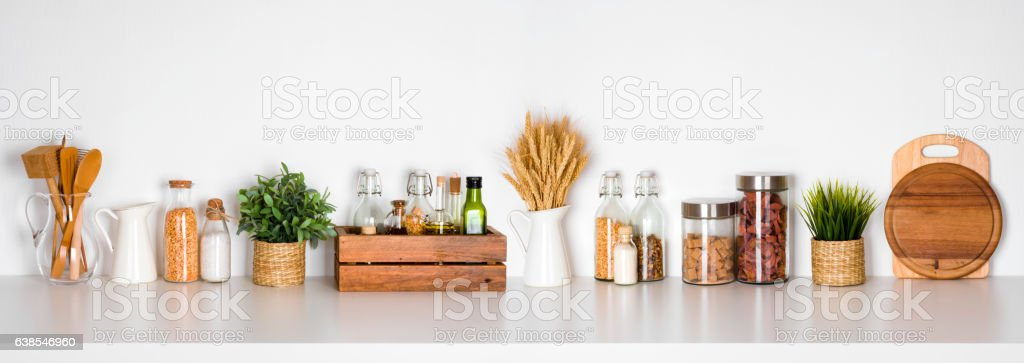Kitchen shelf with various herbs, spices, utensils on white background stock photo