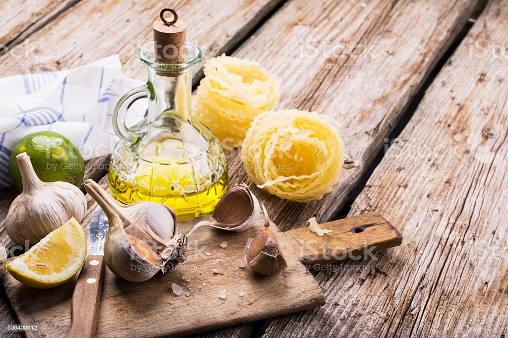 Kitchen simple still life of pasta, olive oil, fresh garlic stock photo