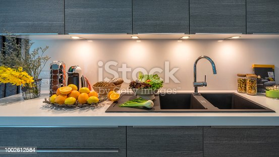 istock Kitchen sink in modern house kitchen with vegetables. Internal view of a modern kitchen. Interior design kitchen beautiful perspective. Quick to prepare meals. 1002612584