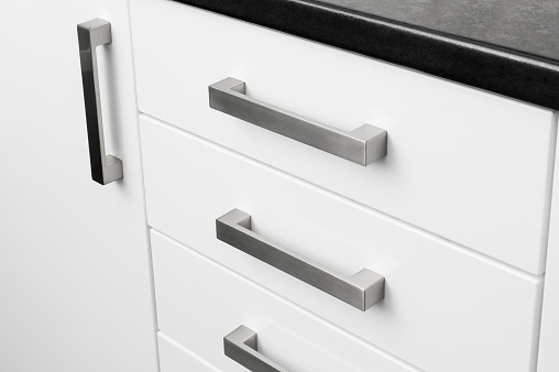 Close-up metal handles on kitchen cupboard units.