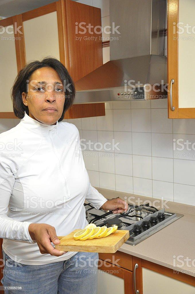 Kitchen Stove Woman holding Lemon Slices royalty-free stock photo