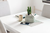 Picture of a kitchen table with a laptop, a smart phone, vase with cactus in it, and a cup of coffee