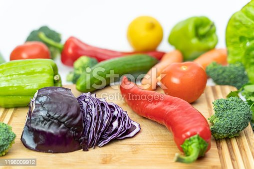 923629650 istock photo Kitchen table with vegetables and cutting board for preparing salad 1196009912