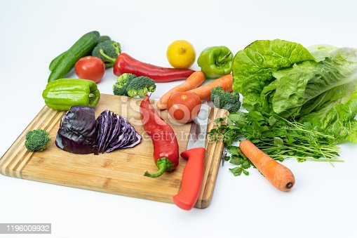 923629650 istock photo Kitchen table with vegetables and cutting board for preparing salad 1196009932