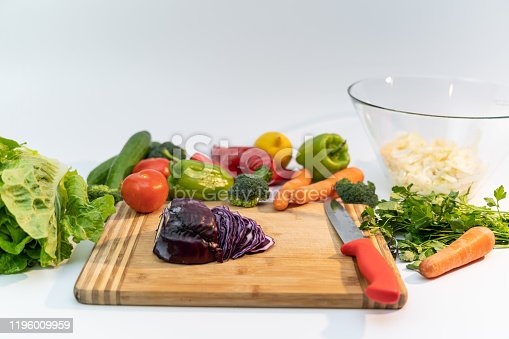 923629650 istock photo Kitchen table with vegetables and cutting board for preparing salad 1196009959
