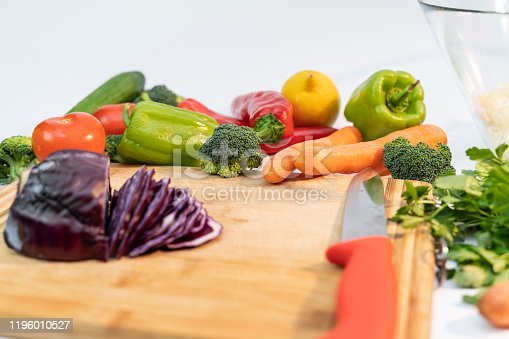 923629650 istock photo Kitchen table with vegetables and cutting board for preparing salad 1196010527