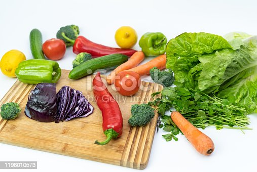 923629650 istock photo Kitchen table with vegetables and cutting board for preparing salad 1196010573