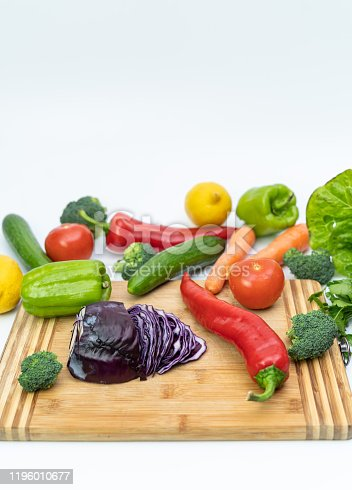 923629650 istock photo Kitchen table with vegetables and cutting board for preparing salad 1196010677
