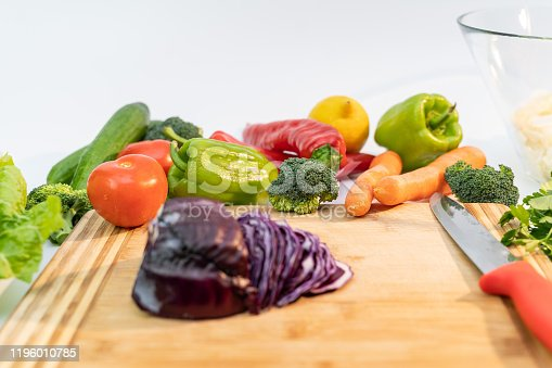 923629650 istock photo Kitchen table with vegetables and cutting board for preparing salad 1196010785