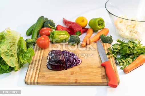923629650 istock photo Kitchen table with vegetables and cutting board for preparing salad 1196010861
