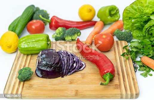 923629650 istock photo Kitchen table with vegetables and cutting board for preparing salad 1196010872