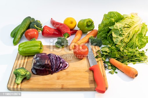 923629650 istock photo Kitchen table with vegetables and cutting board for preparing salad 1196010974