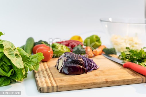 923629650 istock photo Kitchen table with vegetables and cutting board for preparing salad 1196011680