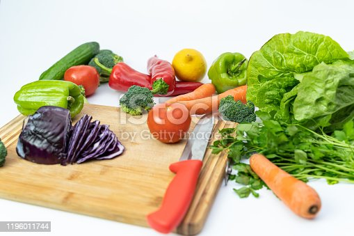 923629650 istock photo Kitchen table with vegetables and cutting board for preparing salad 1196011744
