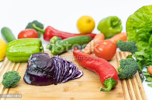 923629650 istock photo Kitchen table with vegetables and cutting board for preparing salad 1196011813