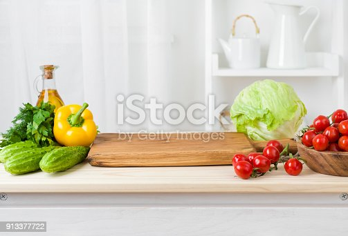 923629650 istock photo Kitchen table with vegetables and cutting board for preparing salad 913377722