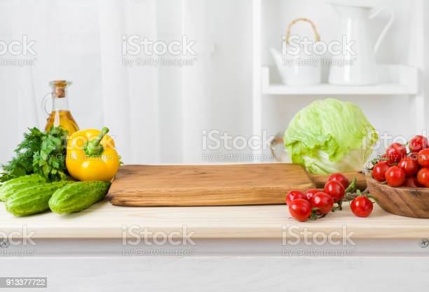 Kitchen table with vegetables and cutting board for preparing salad picture id913377722?b=1&k=6&m=913377722&s=612x612&h=ky3n8 dheoydnsky xe8xq g4v4ltv6cyutuiklnm6e=