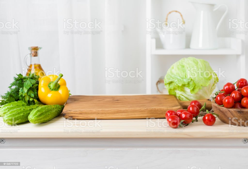 Kitchen table with vegetables and cutting board for preparing salad stock photo