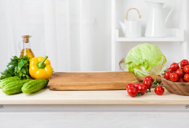 küchentisch mit gemüse und schneidebrett für die zubereitung von salat - gemüsefond stock-fotos und bilder