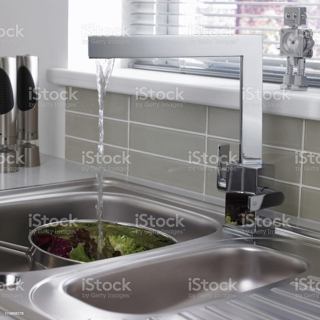 Kitchen tap running water washing lettice in the sink stock photo