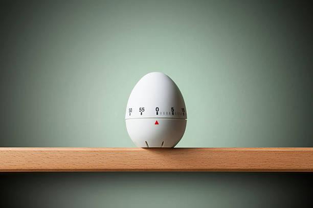 Kitchen timer Kitchen egg timer on the shelf. timer stock pictures, royalty-free photos & images