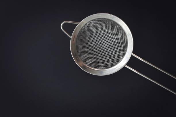 küchenhelfer sieb mehl oder zucker filter draufsicht auf schwarzem hintergrund - puderzuckersieb stock-fotos und bilder