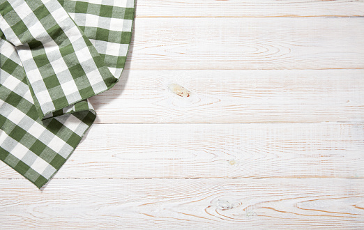 istock Kitchen towel on empty wooden table. Napkin close up top view mock up for design. Kitchen rustic background. 1175721209