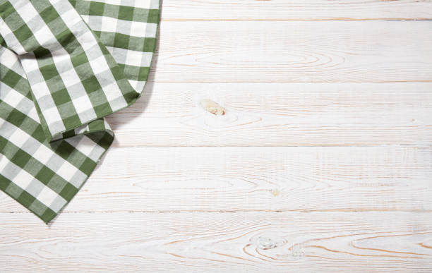Kitchen towel on empty wooden table. Napkin close up top view mock up for design. Kitchen rustic background. Kitchen towel on empty wooden table on white background. Napkin close up top view mock up for design. . table top view stock pictures, royalty-free photos & images