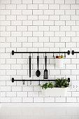 kitchen utensil hanger on white brick wall