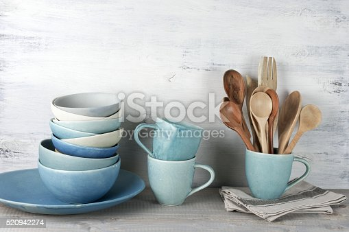 Simple rustic handmade blue crockery against white wooden wall: dish, stack of bowls. mugs and wooden cooking utensils set.