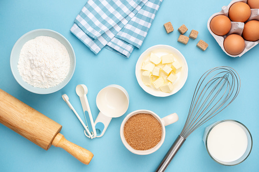 Kitchen utensils and baking ingredients on blue background. Retro style baking and cooking flat lay, table top view