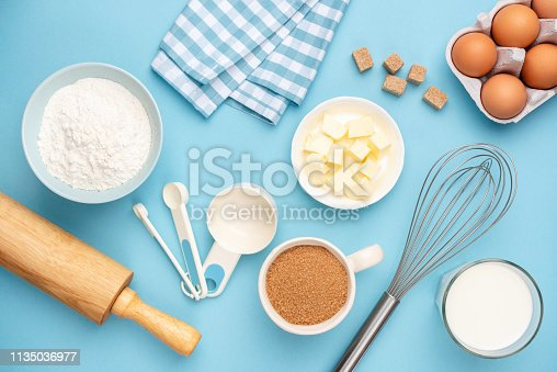 istock Kitchen utensils and baking ingredients on blue background 1135036977