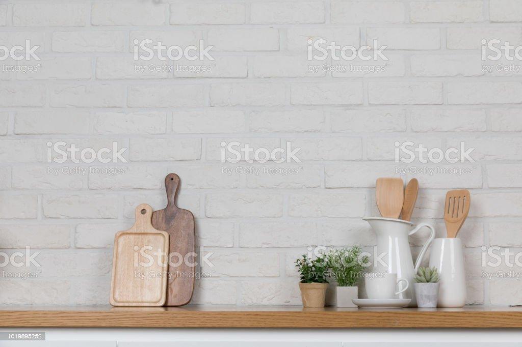Kitchen utensils and dishware on wooden shelf. Kitchen interior...
