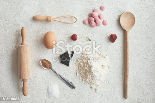 Kitchen ingredients and utensils on white background: rolling pin, wire whisk, four, egg, spoons and chocolate. Also, fruit - cherry and strawberry.
