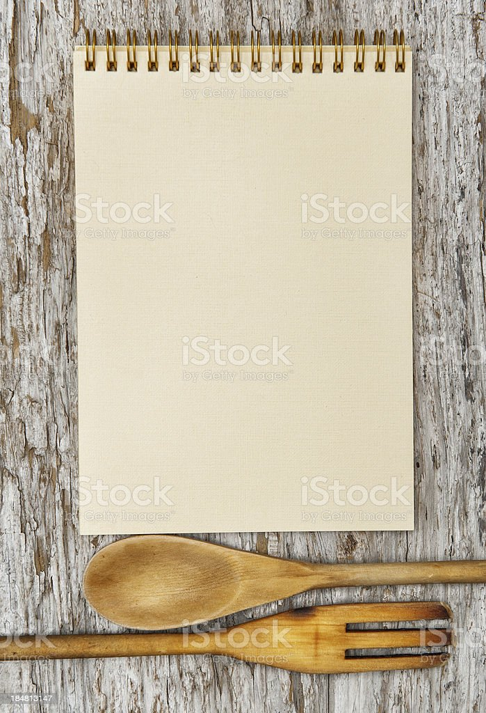 Kitchen utensils and paper spiral notebook on the old wood royalty-free stock photo