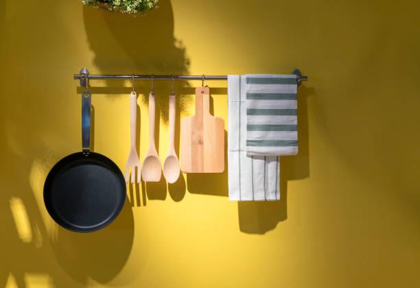 keukengerei en handdoek opknoping op metalen rek tegen een gele achtergrond. - pan keukengereedschap stockfoto's en -beelden