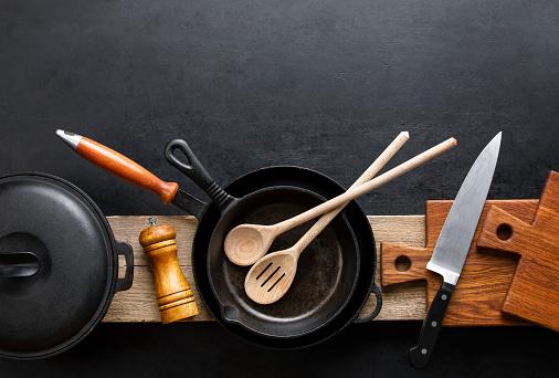Kitchen utensils dark background with cast iron black kitchenware