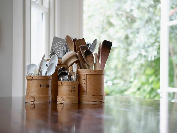 kitchen utensils in containers on table - keukengereedschap stockfoto's en -beelden