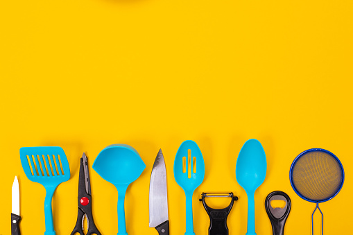 Kitchen utensils isolated on yellow background