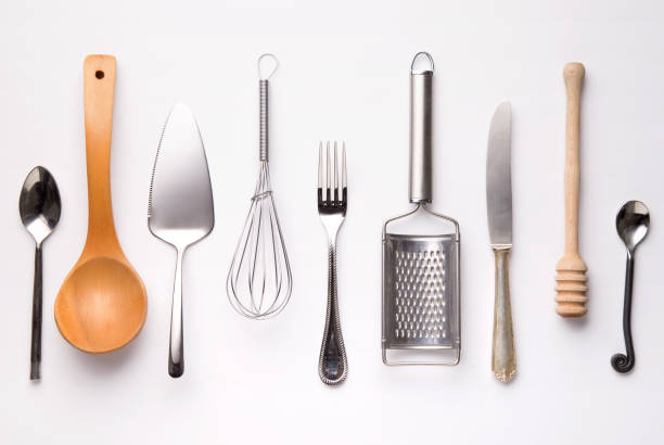 Kitchen utensils, metal and wooden, isolated on white background. Spoons, fork, knife, honey spoon, grinder, whisker. Top view stock photo