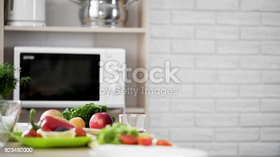 istock Kitchen view with microwave oven and fresh vegetables and fruit on the table 923492000