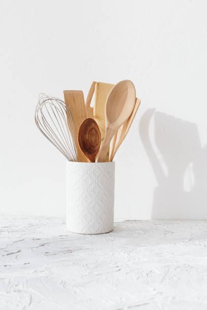 Küche weißes Geschirr Holzutensilien auf dem Tisch. – Foto