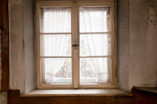 Kitchen window of a 300 years old farmhouse. Window with curtains and view in the garden.