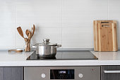 Black ceramic induction stove with timer on control panel and saucepan on top. Contemporary home with modern interior, built in kitchen appliance and white tile on wall with copy space