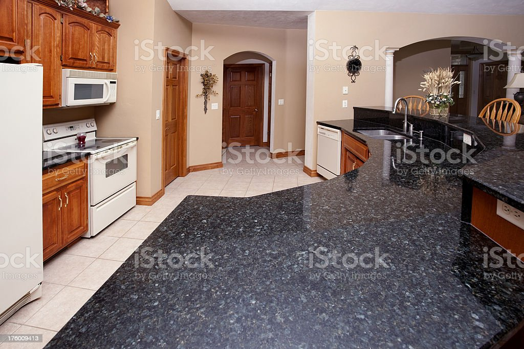 This casual eat-in kitchen has a granite half-circle counter and...